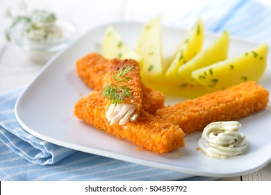 Crispy fish fingers of breaded pollack fillet served with parsley potatoes and remoulade sauce on a white plate
