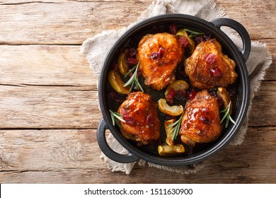 Crispy fragrant baked chicken thighs with apples, cranberries and rosemary closeup in a pan on the table. horizontal top view from above