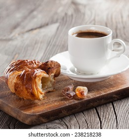 Crispy fresh croissant and cup of coffeee on a dark wooden background, selective focus