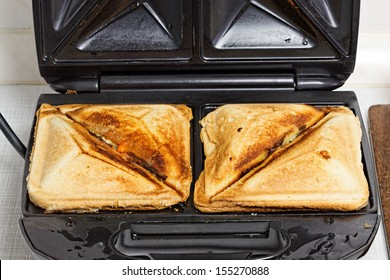 Crispy fresh toasted cheese toasts in sandwich maker.