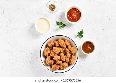 Crispy fried breaded chicken bites in bowl and sauce over light stone background with copy space. Tasty chicken nuggets. Top view, flat lay