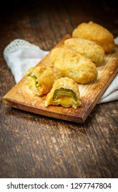 Crispy fried cheddar cheese jalapeno popper bites served on wooden cedar plate with dark moody lighting