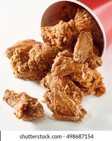 Crispy fried chicken falling from bucket