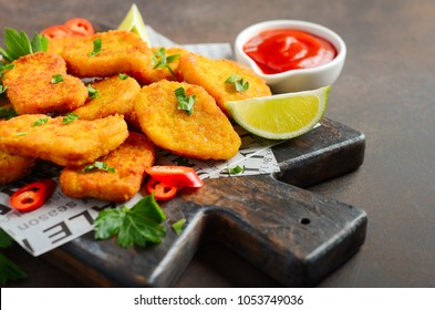 Crispy Fried Chicken Nuggets with Tomato Sauce on Dark Background Selective Focus