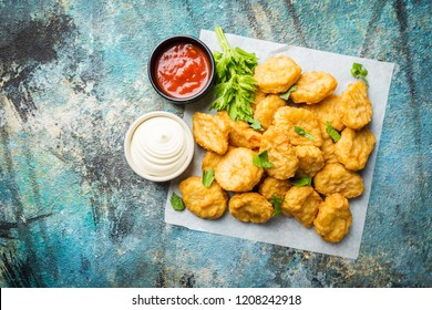 Crispy fried chicken nuggets with tomato sauce. Top view. blue background