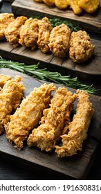 Crispy fried chicken parts on old dark wooden table.
