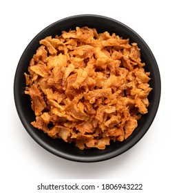 Crispy fried onions in a black ceramic bowl isolated on white. Top view.
