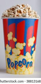 crispy fried popcorn in big striped box on a gray background