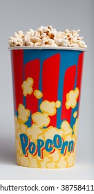 crispy fried popcorn in striped box on a gray background