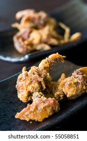 Crispy fried soft shell crab from a Japanese menu, served on dark plate