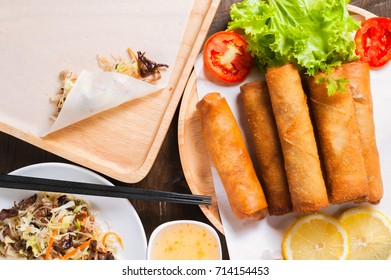 Crispy fried spring rolls with plum sauce and salad, lemon slices on wooden table