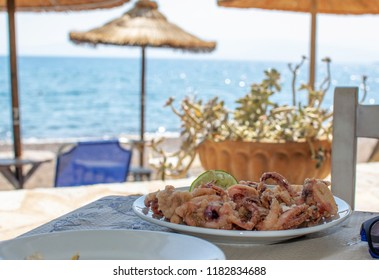 Crispy fried squid rings served on a plate at a seaside restaurant.