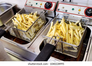 Crispy golden potato chips draining in wire metal baskets on an electric deep fryer in the kitchen of a restaurant