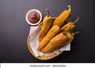 Crispy Green Chilli Pakora or Mirchi Bajji, served with tomato ketchup over moody background. Its a popular tea time snack from India especially in Monsoon. Selective focus