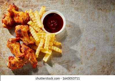 Crispy grilled hot chili pepper chicken wings with oven baked crinkle cut potato chips served with a piquant dip on an old metal background viewed top down