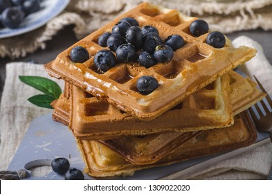 Crispy homemade waffles with berries, topped maple syrup