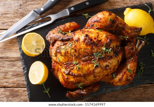 Crispy juicy rotisserie chicken close-up on a slate board on the table. Holiday dish. Horizontal top view from above