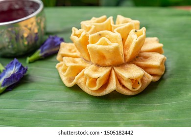 Crispy lotus blossom cookies on a green leaf. Thai traditional snack. Thai homemade cookies.