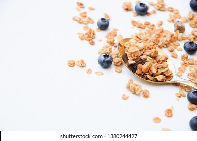 Crispy muesli and blueberry on a spoon Breakfast cereal isolated on white background, selective focus, top view.