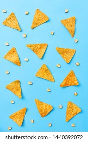 Crispy Nacho chips arranged in a pattern with corn beans on blue pastel background