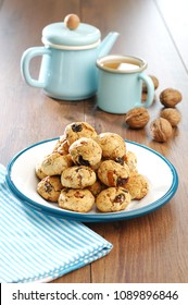 crispy oatmeal cookies with walnuts on an enamel plate on a wooden table with a cup of tea and teapot on the background, blue napkin, wallnuts in shell, no sugar