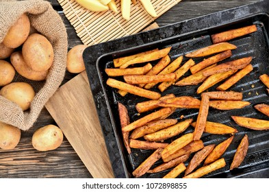 Crispy Oven Baked French Fries for healthy.French fries in black oven tray on wooden board.