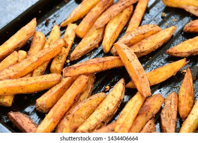 Crispy Oven Baked French Fries. French fries in black oven tray on wooden board.