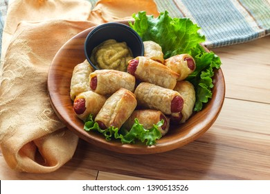 Crispy pigs in a blanket cocktail hotdogs wrapped in croissant dough served with spicy mustard