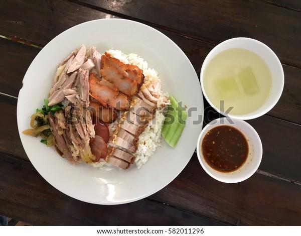 Crispy pork rice with pork leg and red pork on table
