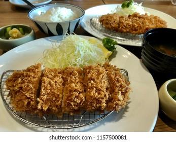 Crispy pork tonkatsu is on a grid. Tonkatsu is a traditional Japanese food.