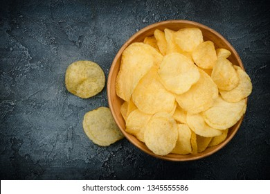 Crispy potato chips in bowl on dark rustic table. Overhead top view with copy space.
