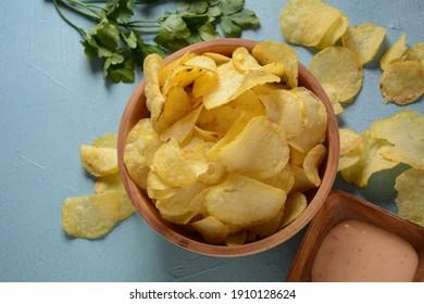 Crispy potato chips in bowl on blue background