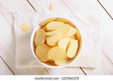 crispy potato chips in a white bowl on white wooden background