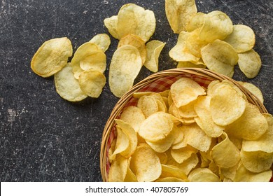 Crispy potato chips in a wicker bowl on old kitchen table