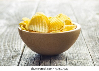 Crispy potato chips in wooden bowl. Salted potato chips.
