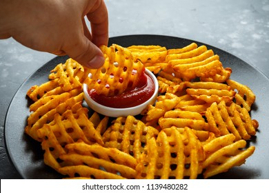 Crispy Potato Waffles Fries with Ketchup in a black plate