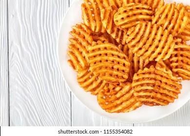 Crispy Potato Waffles Fries, Wavy, Crinkle Cut, Criss Cross Fries on a white plate on a wooden table, view from above, close-up, flat lay