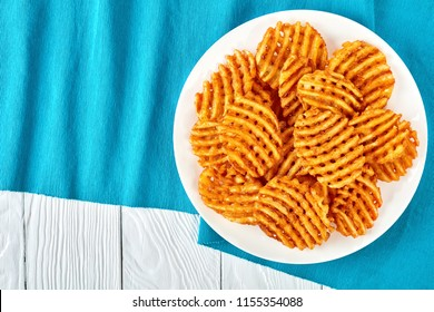 Crispy Potato Waffles Fries, Wavy, Crinkle Cut, Criss Cross Fries on a white plate on a textile table mat on a wooden table, view from above, flat lay