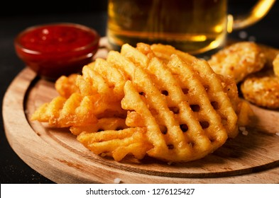 Crispy potato waffles fries, wavy, crinkle cut, criss cross cries with on a cutting board