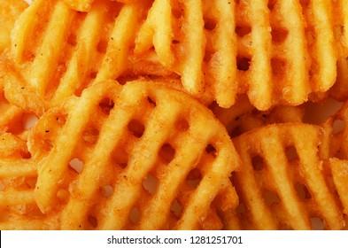 Crispy potato waffles fries, wavy, crinkle cut, criss cross cries as background
