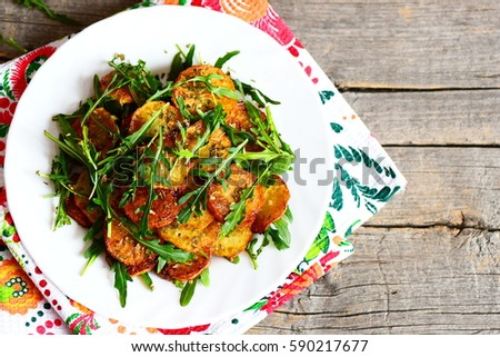 Crispy potatoes with arugula on a plate and wooden background with copy space for text. Round fried potatoes with fresh arugula and condiments. Fast and tasty vegetable dish. Top view