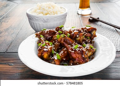 Crispy sesame chicken wings with a sticky sweet Asian sauce and white boiled rice on a plate on wooden table.