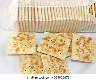 Crispy soda crackers on plate. Open package in background
