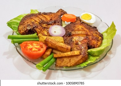 Crispy spicy fried pomfret fish with french fries and garnished with vegetables. A popular Bengali Indian cuisine.