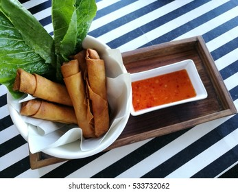 Crispy spring roll with fresh vegetable and sweet chili sauce on the wooden tray