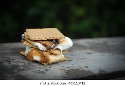 A crispy sticky double stacked smore cooked over an open fire at a summer bbq,