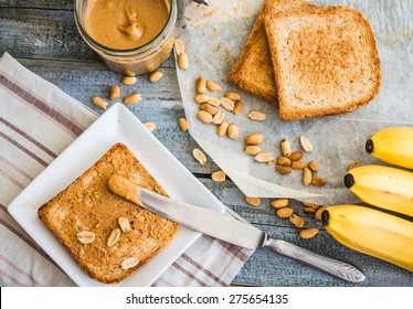 crispy toast with peanut butter, bananas, breakfast on the wooden background, top view