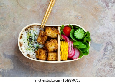 Crispy tofu with rice and salad in bento box