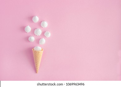 Crispy waffle ice creame cone with scattered white twisted meringues on pink background, greeting card, copy space