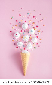 Crispy waffle ice creame cone with scattered white twisted meringues and with confectionary decorations on pink background, greeting card